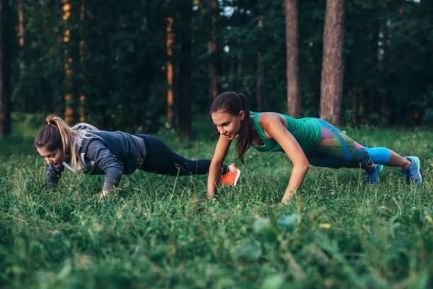 Zwei Freundinnen, die gemeinsam im Wald, Push-up-Übungen auf dem Rasen – Foto