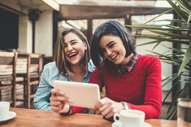 Two Female Frineds Holding Tablet and Laughing in Coffee Shop - Photo