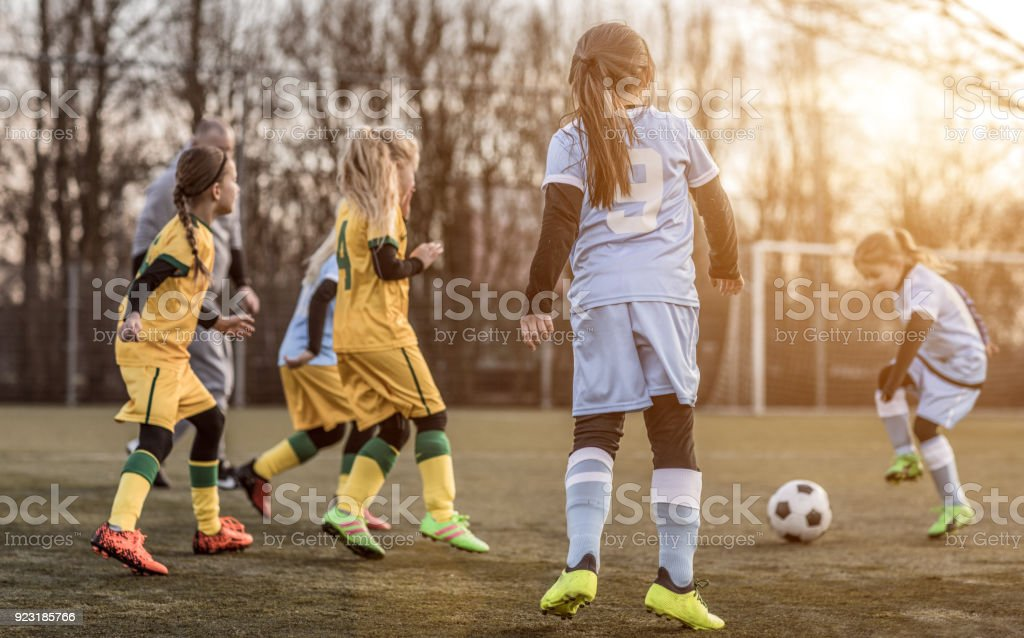 Two Female Girl Soccer Teams playing a football training match in the...