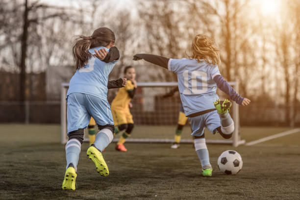 Two Female Girl Soccer Teams playing a football training match in the Spring outdoors stock photo