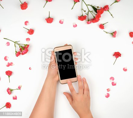 istock two female hands are holding a smartphone with a blank black screen 1155044925