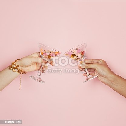 Two female hands holding wine glasses with colorful holiday confetti on pink background. Celebration, party and holidays background