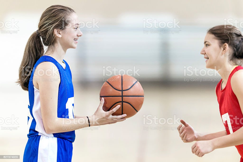 Two female high school basketball players ready to play