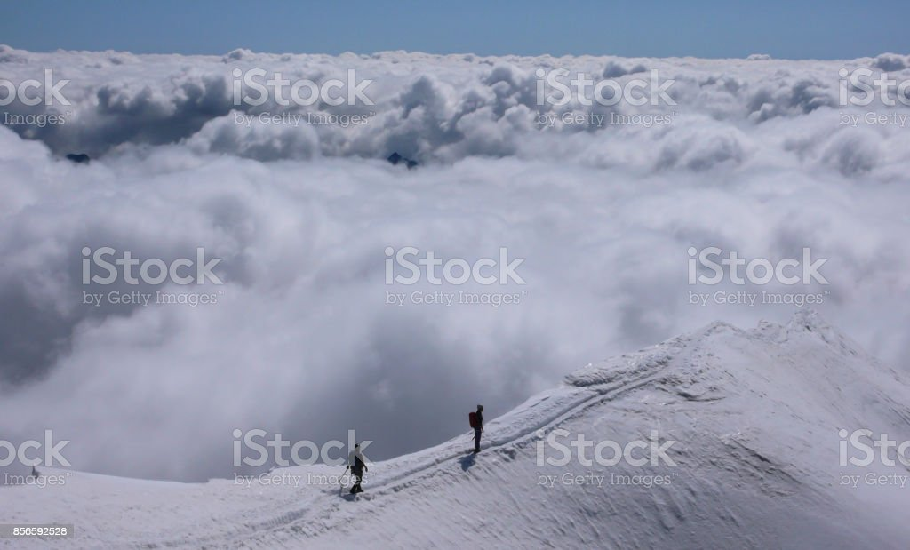 two female mountain climbers on an exposed ridge in the Swiss Alps stock photo