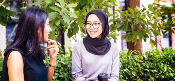 two female muslim friends enjoying conversation in kuala lumpur - скромная одежда стоковые фото и изображения
