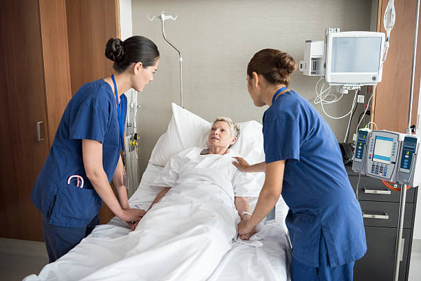 two female nurses reassuring senior woman in hospital bed - australian nurses stock photos and pictures