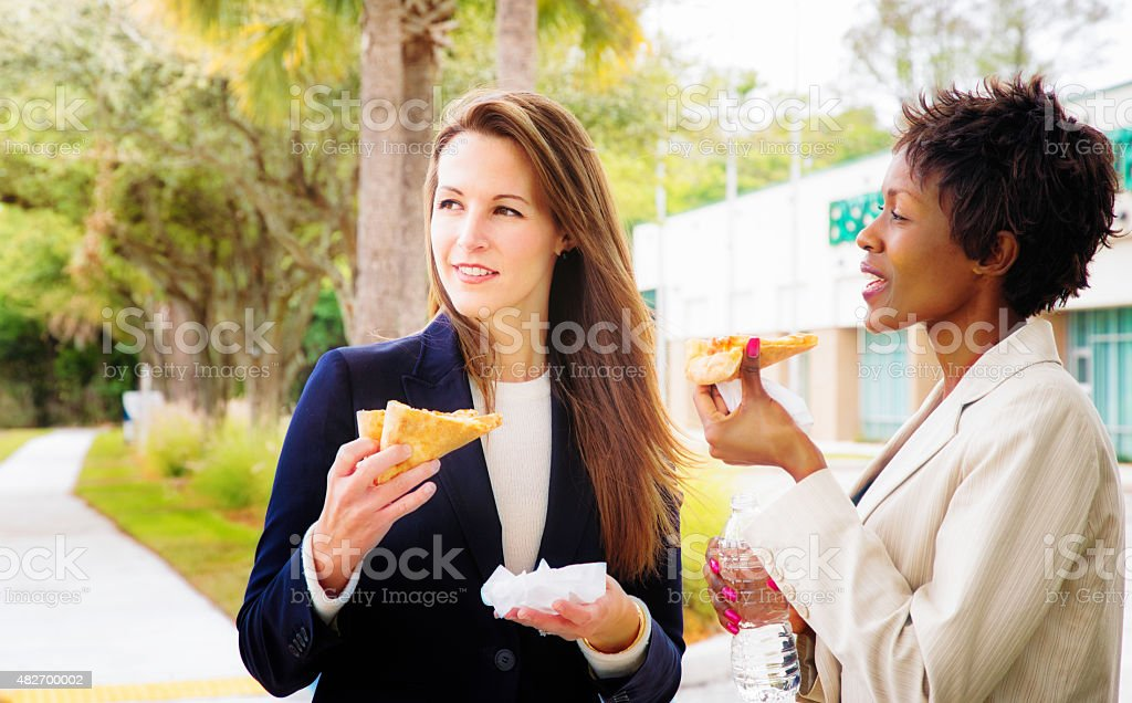 Two female office workers enjoying pizza outdoors lunch break stock photo