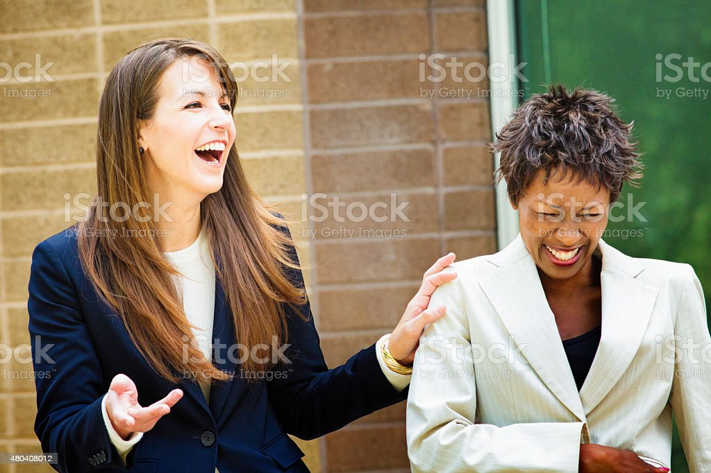 Two female office workers laugh at irresistible joke outdoors stock photo