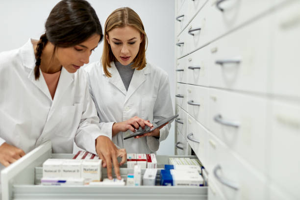 Two female pharmacists sorting medicines in the storage area. stock photo