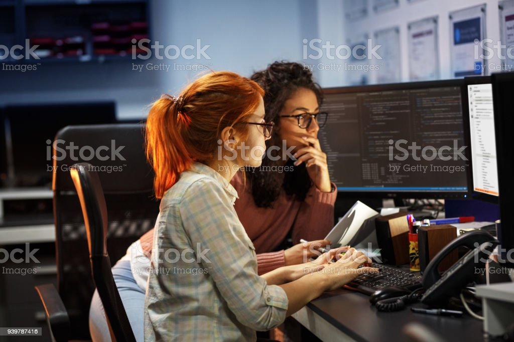 Two female programmers working on new project.They working late at night at the office. stock photo
