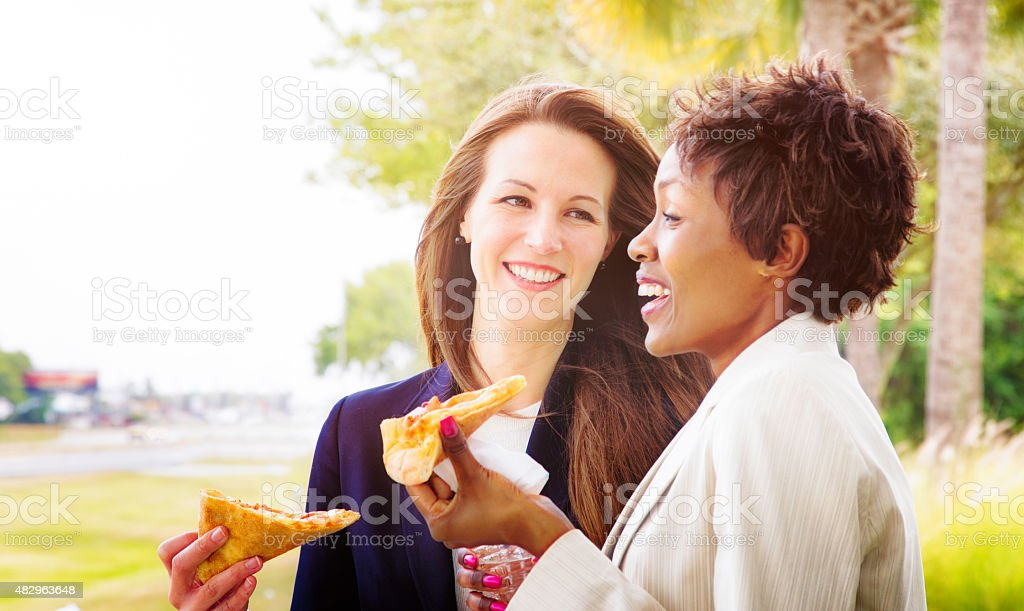 Two female reps laugh while eating pizza outdoors during event stock photo