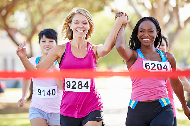 two female runners finishing race together - marathon stock photos and pictures