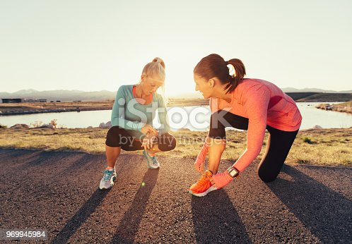 The female runners in blue and pink shirts and running shoes are talking before their run at sunset in a suburban park in Salt Lake City, Utah. These women are friends who love to train together. One woman is getting her watch ready and the other is tying her shoe. Running is their favorite way to exercise.