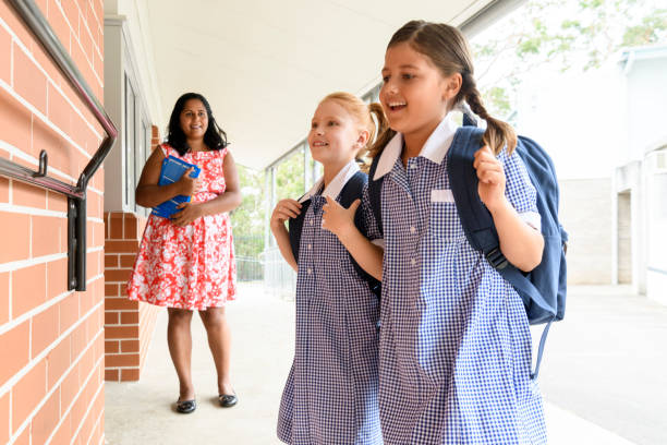 Two female school friends with backpacks and teacher in background stock photo