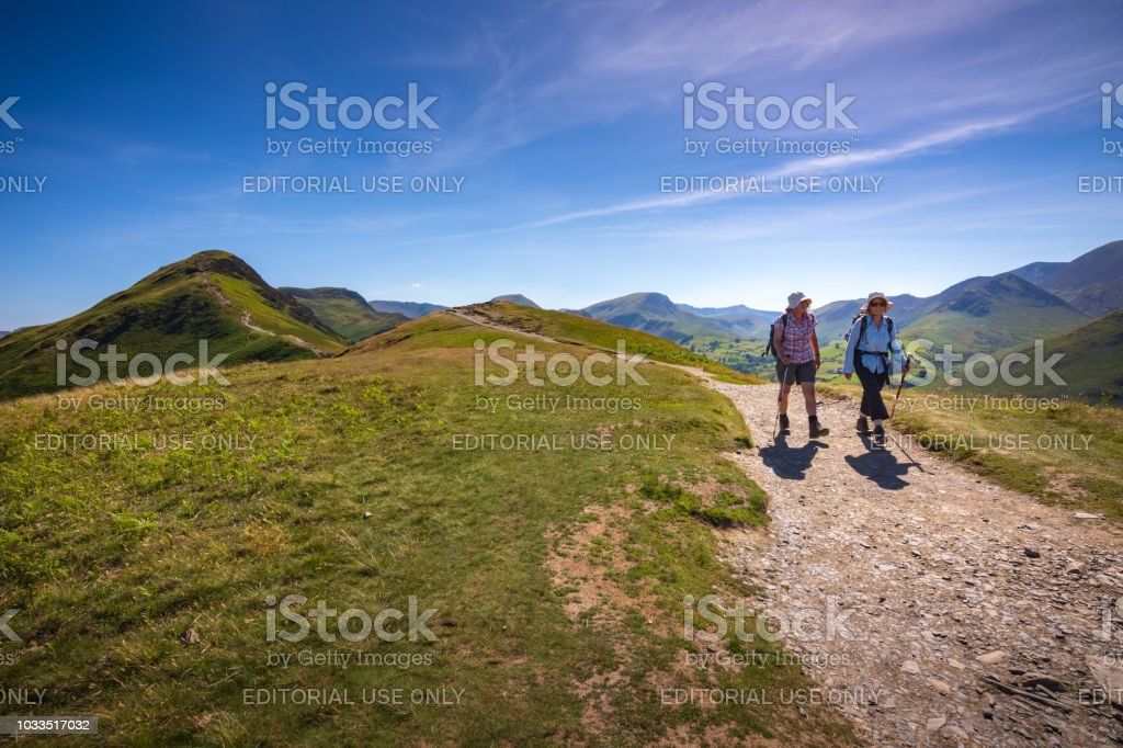 Two female senior hikers descend Cat Bells fell in Keswick, England stock photo