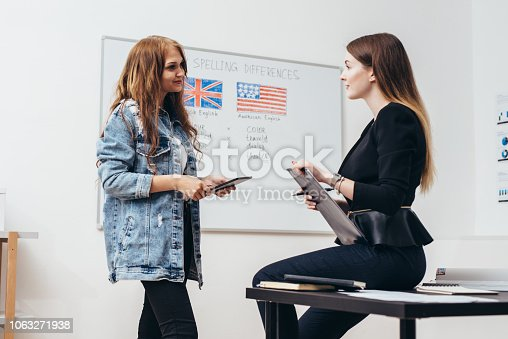 Two female students talking in classroom. College, English language school