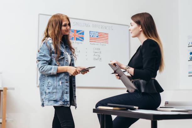 Zwei Studentinnen im Klassenzimmer zu sprechen. Hochschule, Englisch-Sprachschule. – Foto