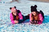 Happy friends having fun lying on snow in winter park