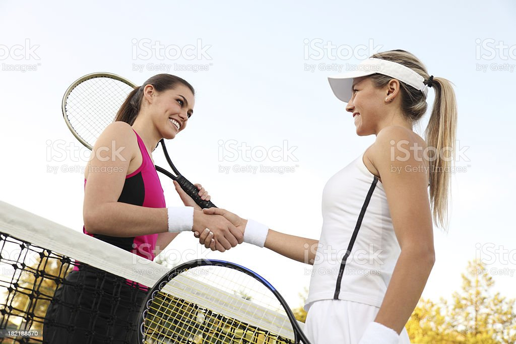 Two female tennis players shaking hands in victory stock photo