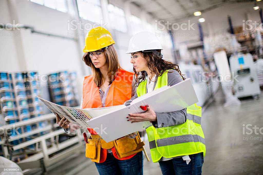 Two female workers choosing the color at the color palette stock photo