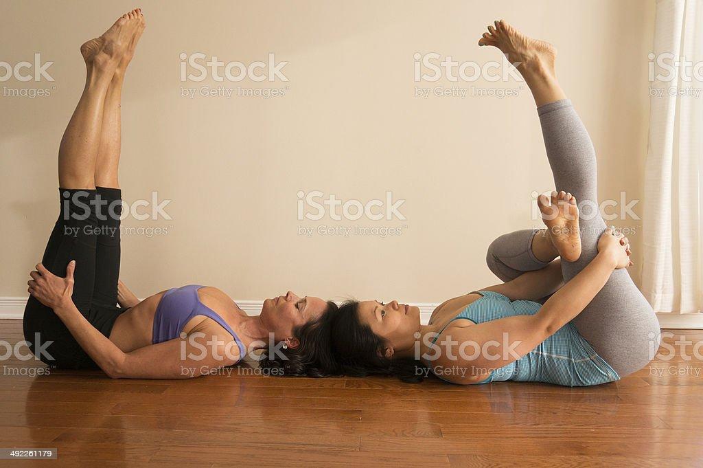 Dos mujeres haciendo Yoga médico en la pierna plantear dos camas dobles  foto de stock libre d08eb3fbee57