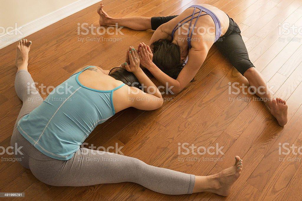 Dos mujeres haciendo Yoga médico en gran angular sentado doblado hacia  adelante foto de stock libre 66ba810aedc6