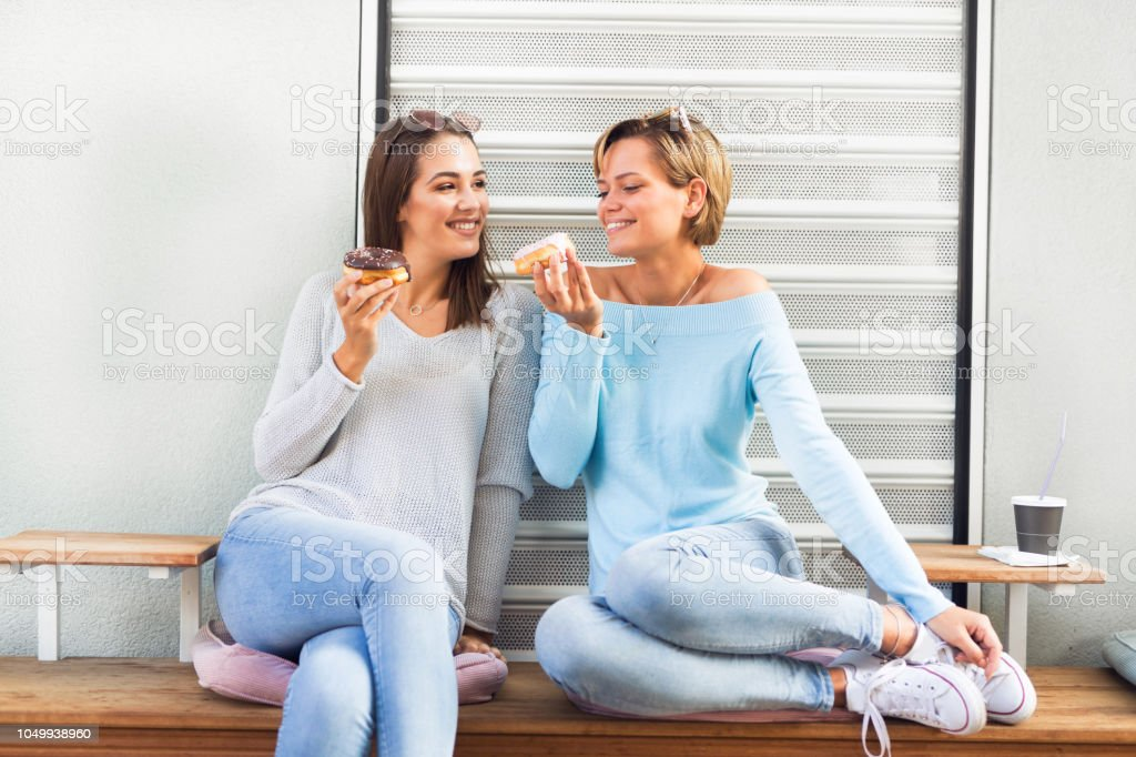 Two females eating donuts laughing and having fun stock photo