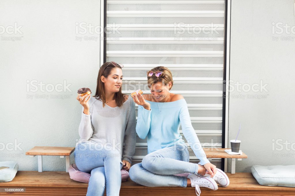 Two females eating donuts stock photo