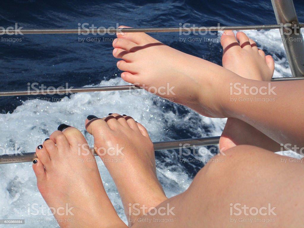 Two Female's feet relaxing on a boat zbiór zdjęć royalty-free