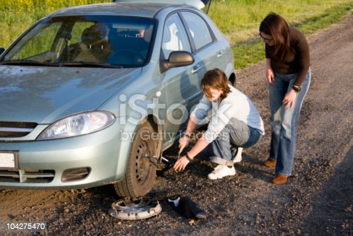istock Two females fixing a broken tire on the side of the road 104275470