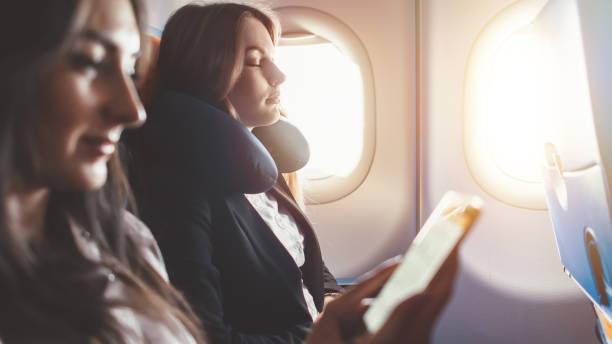 Zwei Frauen gehen auf Geschäftsreise Reise mit dem Flugzeug. Eine Frau liest ein e-Book auf einem smartphone – Foto