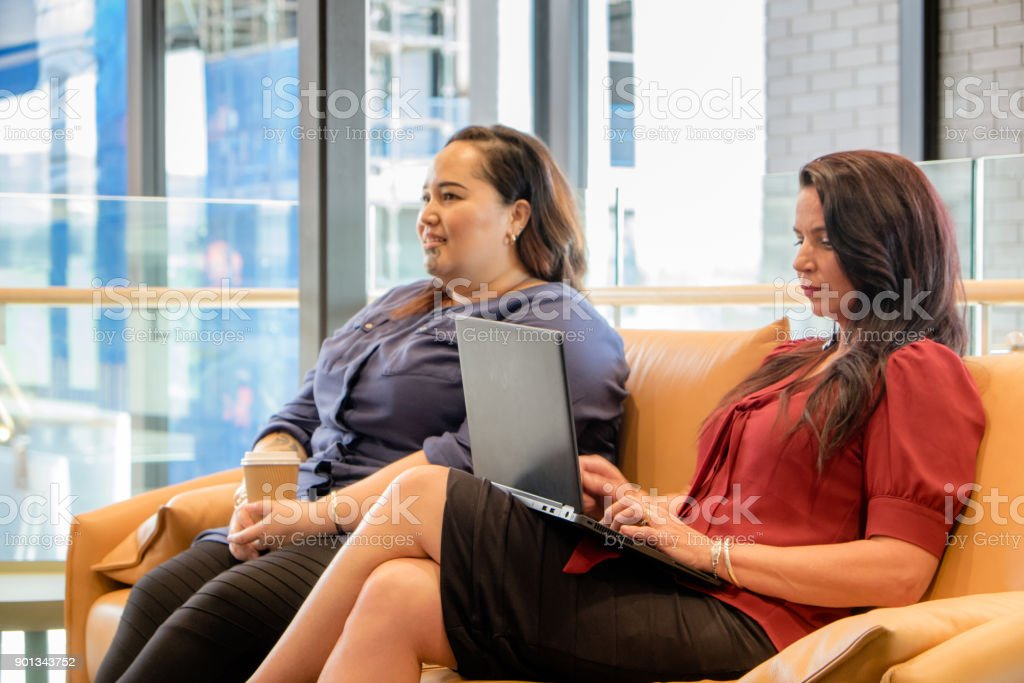 Two females sitting on couch in waiting room, office lounge or business reception area - could be candidates for job interview. Caucasian female is working on laptop computer; Maori woman has tattoos including facial to moko. stock photo