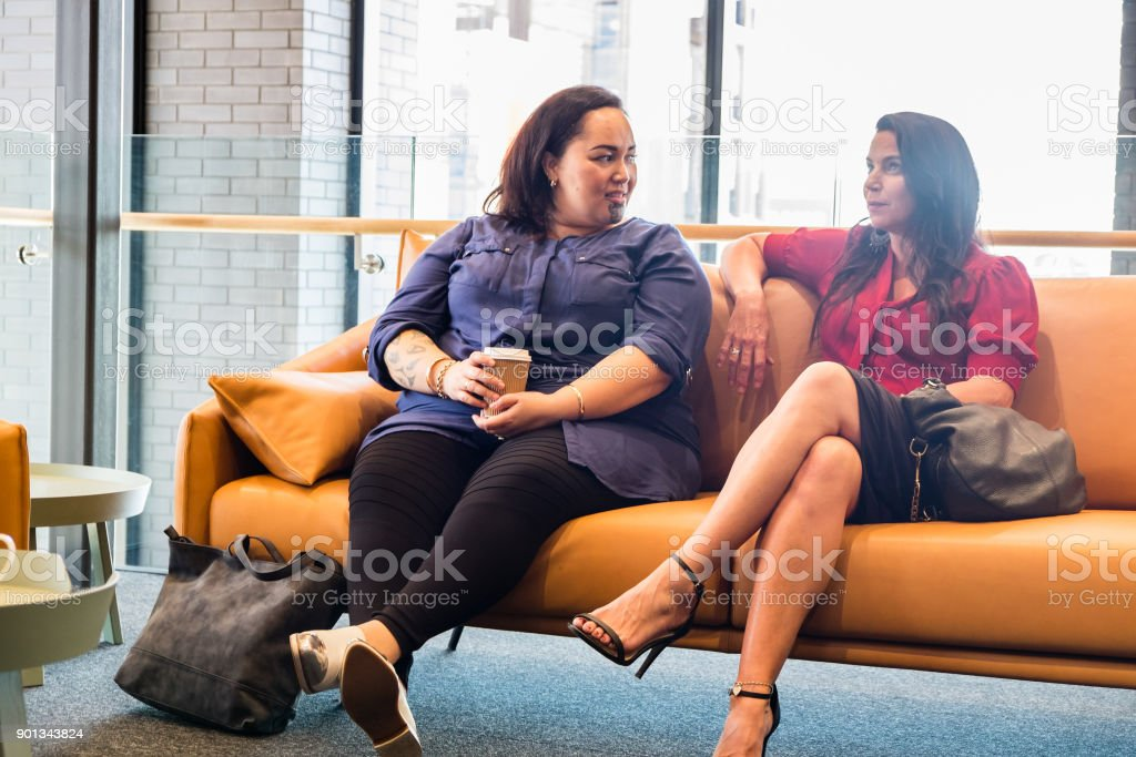 Two females sitting on couch in waiting room, office lounge or business reception area - could be candidates for job interview. Photographed in Auckland, New Zealand, NZ. stock photo