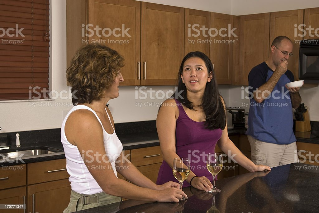 Two females talking while a male eats food stock photo