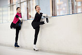 Full length portrait of two teenage girls stretching during figure skating practice in indoor rink, copy space