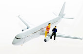 Two figurines sitting on airplane wing on white background.