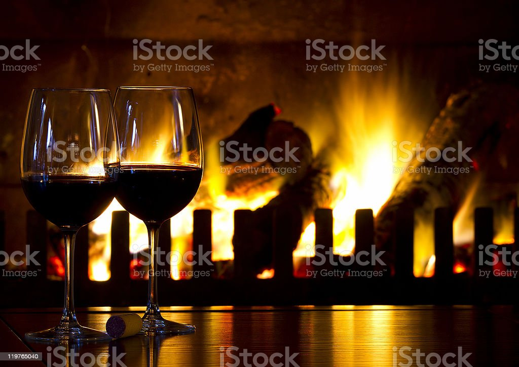 Two filled wine glasses near burning fireplace stock photo