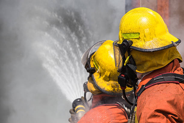 two firefighter in helmet and oxygen mask spraying water – Foto