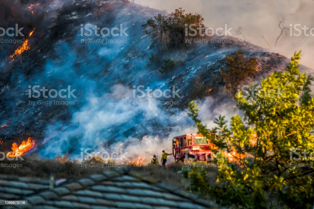 Two Firefighters and Bulldozer with Brushfire Burning Hillside stock photo
