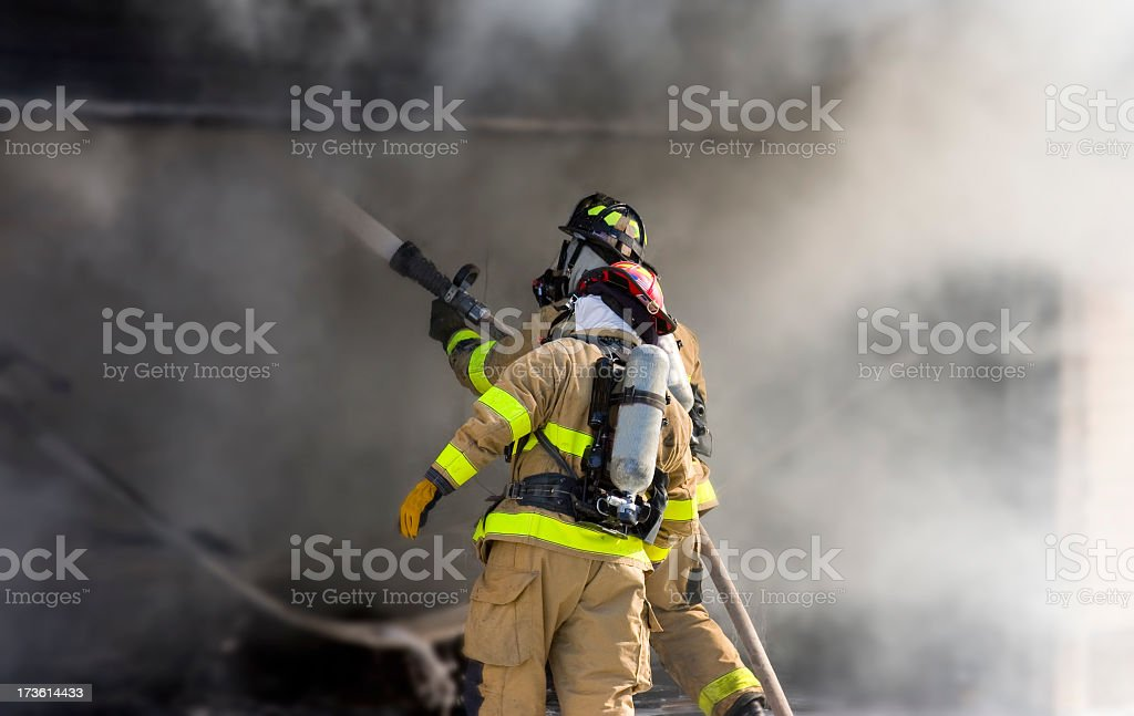 Two firefighters at work putting out a fire Two firefighters putting out a fire. Accidents and Disasters Stock Photo