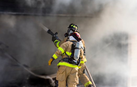 Two Firefighters At Work Putting Out A Fire Stock Photo - Download Image Now