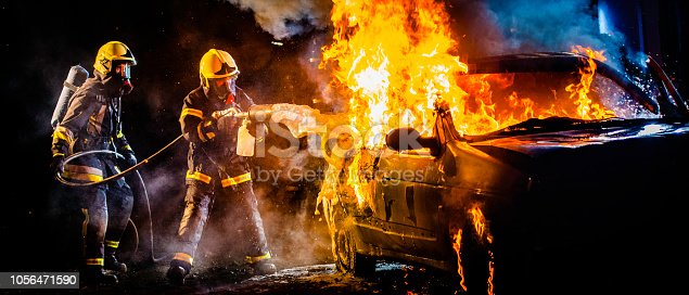 Panoramic photo of two firemen spraying foam on a burning car in flames at night.