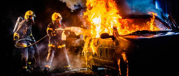 Zwei Feuerwehrleute Löschen einer brennenden Auto mit Schaum – Foto