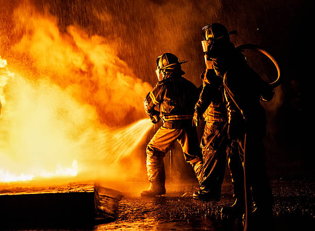 two firefighters fighting a fire with a hose and water - bombero fotografías e imágenes de stock