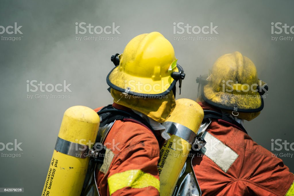 two firefighters fire fighting suround with dark smoke stock photo