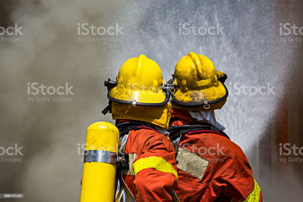 zwei Feuerwehrleute Feuer kämpfen Surround mit dunkler Rauch – Foto