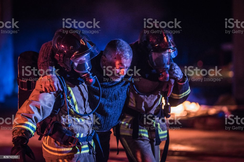 Two firefighters helping victim stock photo