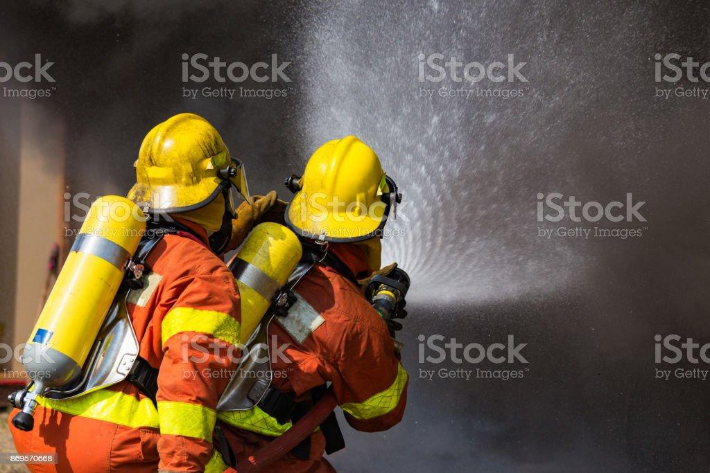 dois bombeiros de spray de água por alta pressão bocal surround com fumaça escura - foto de acervo