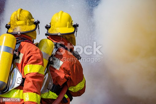 istock two firefighters water spray by high pressure nozzle surround with dark smoke 869570728