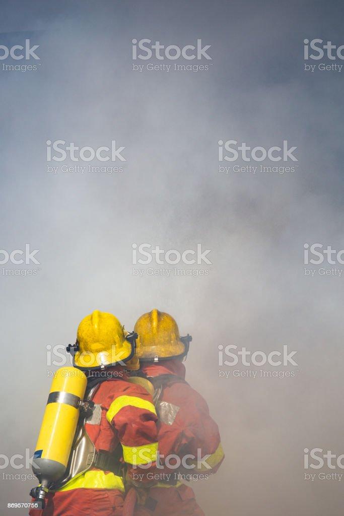 zwei Feuerwehrleute Wasserspray Hochdruck Düse Surround mit dunkler Rauch – Foto